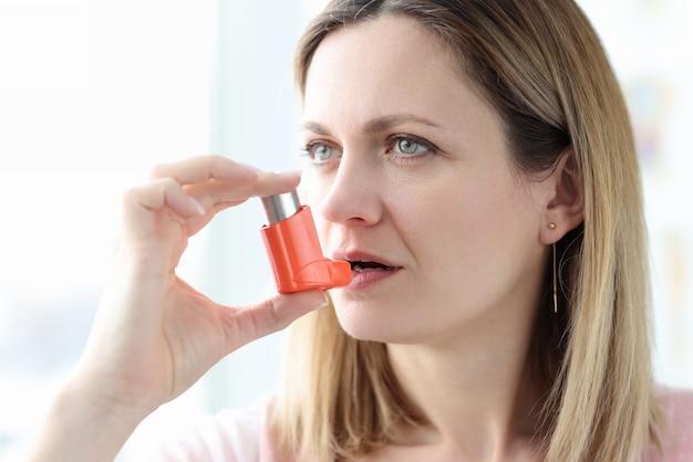 Zieke vrouw met hormooninhalator in de buurt van mond. behandeling van bronchiale astma-concept