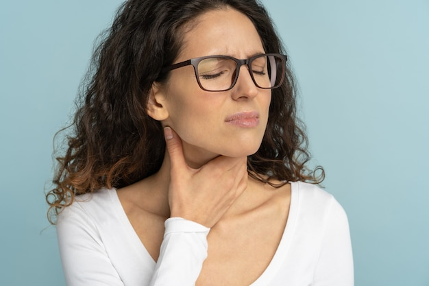 Zieke vrouw met keelpijn, amandelontsteking, die lijden aan pijnlijk slikken geïsoleerd in studio