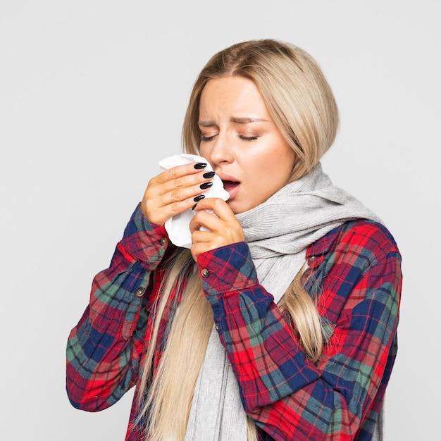 Zieke vrouw met papieren servet niezen