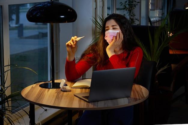 Zieke vrouw met pillen en thermometer op een tafel werken op een laptop vanuit huis op quarantaine-isolatie.