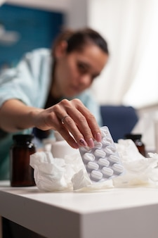 Zieke vrouw met seizoensgebonden ziekte thuis zittend in deken op de bank jonge volwassene die medicijnen neemt en...