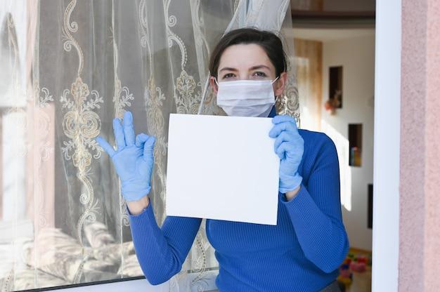 Zieke vrouw met virus bescherming gezichtsmasker en handschoenen kijkt uit het raam