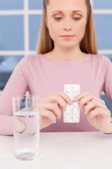 Zieke vrouw. nadenkende jonge vrouw die medicijnen vasthoudt en wegkijkt terwijl ze aan tafel zit