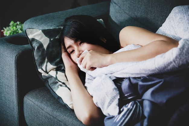 Zieke vrouw omvat met een deken die op de bank ligt