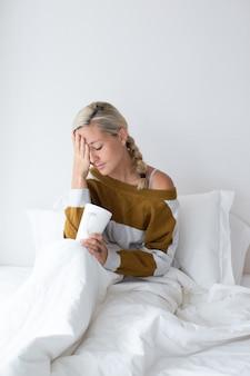 Zieke vrouw op bed zitten en aan het voorhoofd raken
