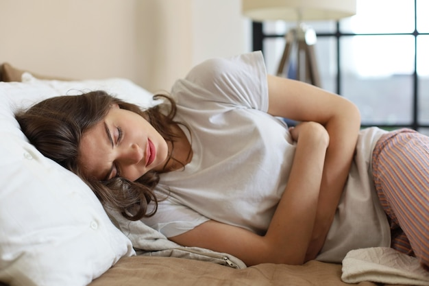 Zieke vrouw op bedconcept buikpijn.