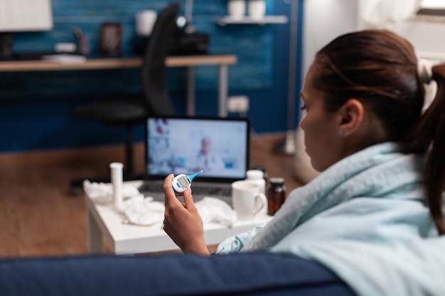 Zieke vrouw op online conferentie met arts thuis