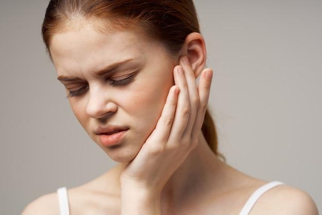 Zieke vrouw slechte gehoorstoornissen in witte t-shirts lichte achtergrond