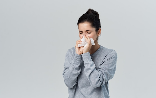 Zieke vrouw snuit haar neus met servet en warme trui