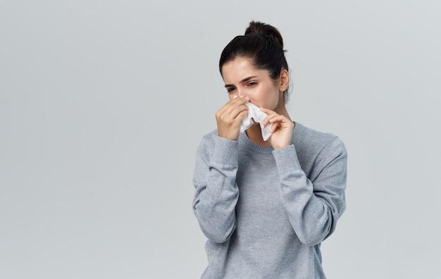 Zieke vrouw snuit haar neus met servet