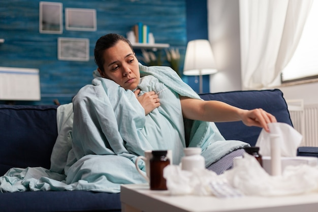 Zieke vrouw thuis in een deken gewikkeld met virusinfectie ziekte koorts ziekte griep verkoudheid kaukasisch...
