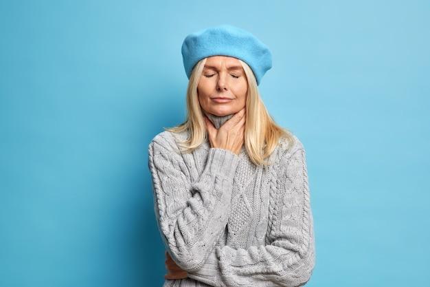 Zieke vrouw van middelbare leeftijd raakt nek lijdt aan keelpijn heeft griepsymptoom sluit ogen om pijn te verlichten staat ongelukkig binnenshuis draagt baret en warme gebreide trui. onaangename gevoelens tijdens het slikken