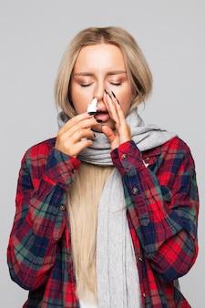 Zieke vrouw van streek in geruit overhemd gewikkeld in sjaal met neusspray om zichzelf te helpen