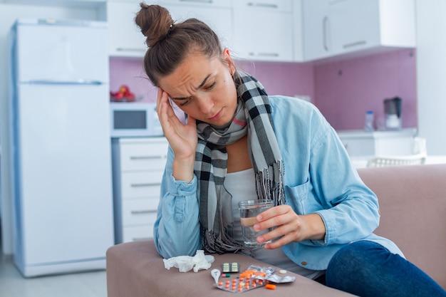 Zieke vrouw verkouden en leed aan hoofdpijn. griep- en koudebehandeling thuis