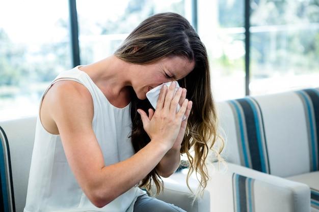 Zieke vrouw, zittend op een bank, niezen in een tissue