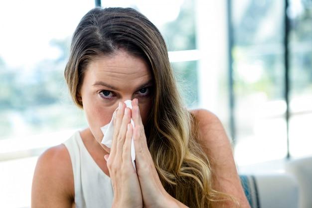 Zieke vrouw, zittend op een bank, snuit haar neus