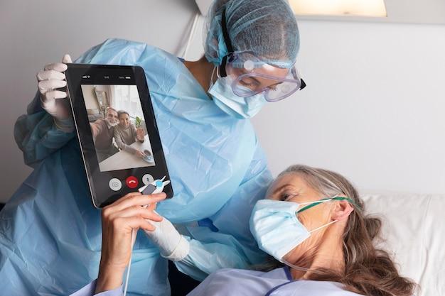 Zieke vrouwelijke patiënt in bed in het ziekenhuis in gesprek met familie via een tablet
