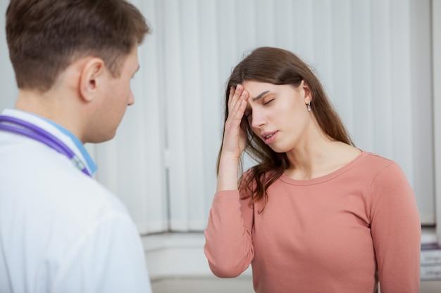 Zieke vrouwelijke patiënt met migraine op medische afspraak