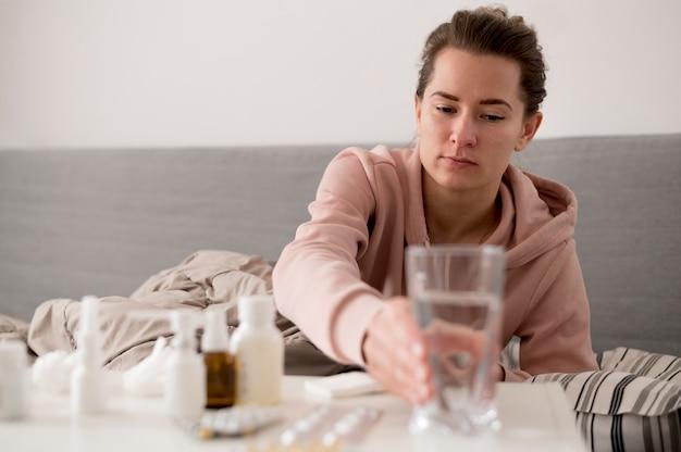 Zieke vrouwelijke persoon die voor een glas water bereikt