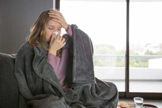 Zieke vrouwen blazende neus met servet, die hand op hoofd houden