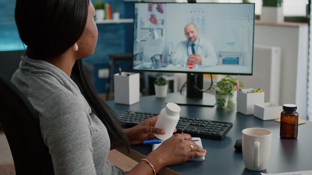 Zieke vrouwenpatiënt die pillenbehandeling voor ademhalingsziekte bespreekt met therapeut tijdens videogesprekconferentievergadering in de gezondheidszorg