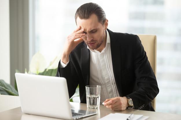 Zieke zakenman die strenge hoofdpijn heeft