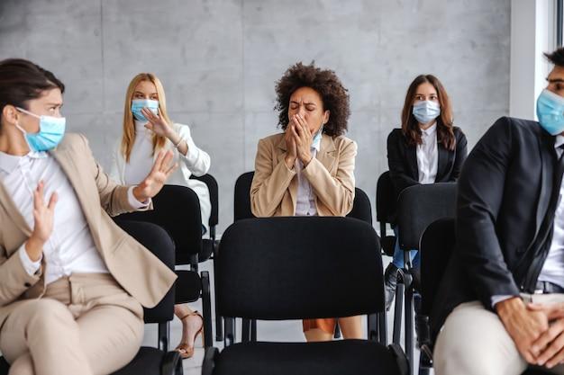 Zieke zakenvrouw hoesten zittend met haar collega's op seminar. collega's zijn bang voor het coronavirus dus verstoppen ze zich.