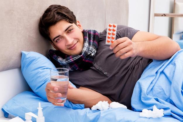 Zieke zieke man in bed met medicijnen en drugs