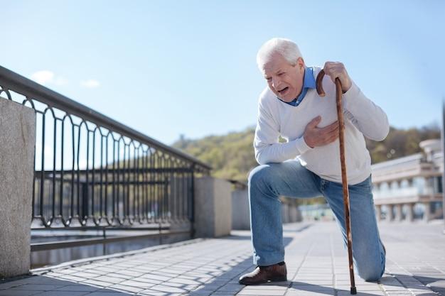 Zieke, zwakke verbaasde man die op de knie staat en op de stok achterover leunt terwijl hij op hulp wacht