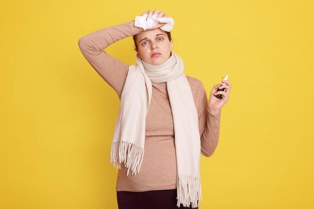 Zieke zwangere vrouw staat geïsoleerd over gele muur, aanstaande mama raakt haar voorhoofd aan, voelt hoofdpijn, houdt servet en neusspray in handen, dame draagt beige overhemd en sjaal.
