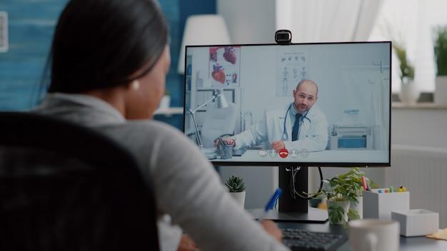 Zieke zwarte vrouw bespreekt met therapeut arts over ziektediagnose die het testresultaat van de kliniek uitlegt op videocall-conferentievergadering