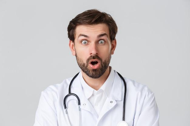Ziekenhuis, gezondheidswerkers, covid-19 behandelingsconcept. close-up van verraste, verbaasde bebaarde arts in witte scrubs en stethoscoop, open mond en zeg wow van geweldig nieuws