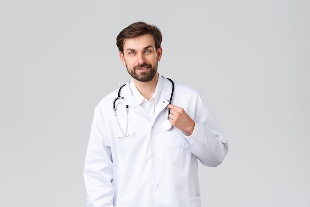 Ziekenhuis, gezondheidswerkers, covid-19 behandelingsconcept. knappe bebaarde dokter in witte scrubs met stethoscoop, glimlachend naar de patiënt, luisterend naar problemen, mensen behandelend in de kliniek