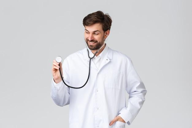 Ziekenhuis, gezondheidswerkers, covid-19 behandelingsconcept. knappe dokter met baard in witte scrubs, met een stethoscoop om de longen van de patiënt te luisteren, cliënten in de kliniek te behandelen, glimlachend, grijze achtergrond