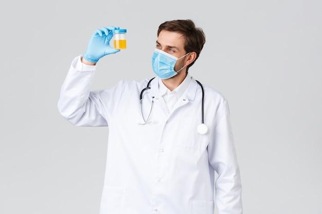 Ziekenhuis, gezondheidswerkers, covid-19 behandelingsconcept. laboratoriumtechnicus in witte scrubs, arts onderzoekt monster urine van patiënten, kijkt naar container met analyse, staande grijze achtergrond