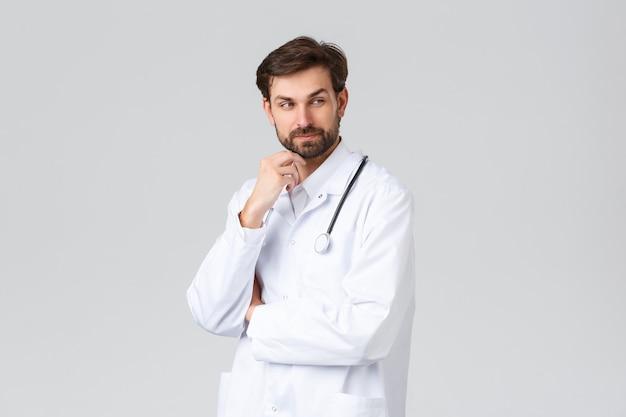 Ziekenhuis, gezondheidswerkers, covid-19 behandelingsconcept. professionele arts, arts in witte scrubs en stethoscoop, kijk weg nadenkend, denkend en wrijvend baard, grijze achtergrond