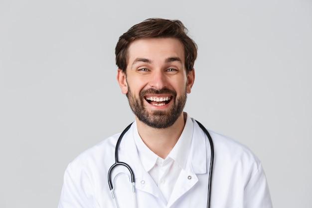 Ziekenhuis, gezondheidswerkers, covid-19 behandelingsconcept. vrolijke bebaarde arts met positieve houding, pauze nemen, glimlachen en lachen tijdens het praten, scrubs dragen, grijze achtergrond staan.