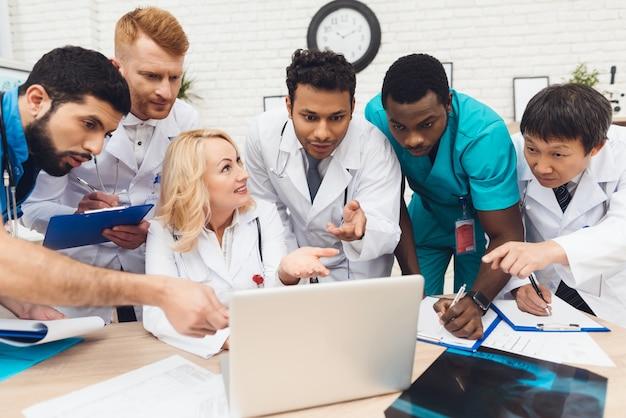 Ziekenhuis multinationale artsen op zoek op laptop.