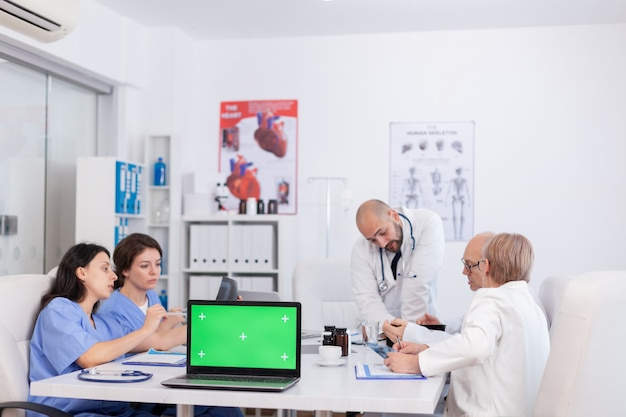 Ziekenhuis teamwerk medisch ontdekkingsvaccin tegen virusziekte in vergaderruimte. mock-up groen scherm chroma key laptopcomputer met geïsoleerde display staande op bureau diagnose analyseren