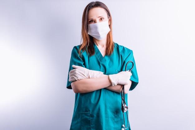 Ziekenhuisarts met een stethoscoop met handschoenen en gezichtsmasker die recht vooruit kijkt op een witte achtergrond
