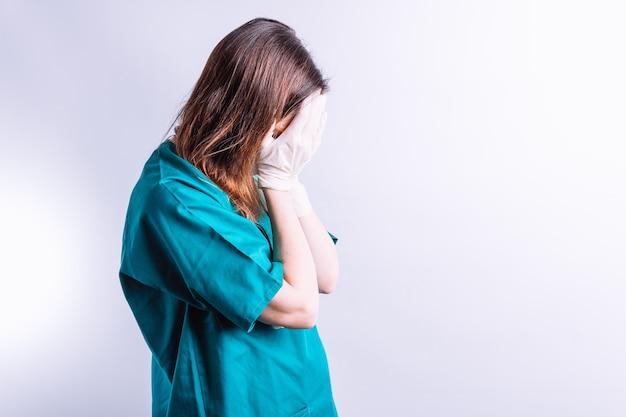 Ziekenhuisarts met gezichtsmasker en handschoenen die haar gezicht bedekken, het symbool van vermoeidheid en slechte resultaten. concept om op de limiet te zijn
