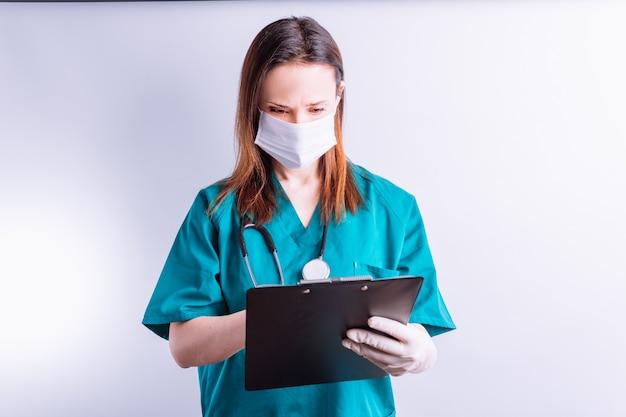 Ziekenhuisarts met maskerhandschoenen op witte achtergrond die een volledig rapportmedicijn leest