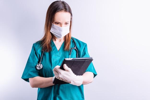 Ziekenhuisarts met stethoscoop en gezichtsmasker die rapporten op een tablet bekijkt. geneeskunde en technologie concept