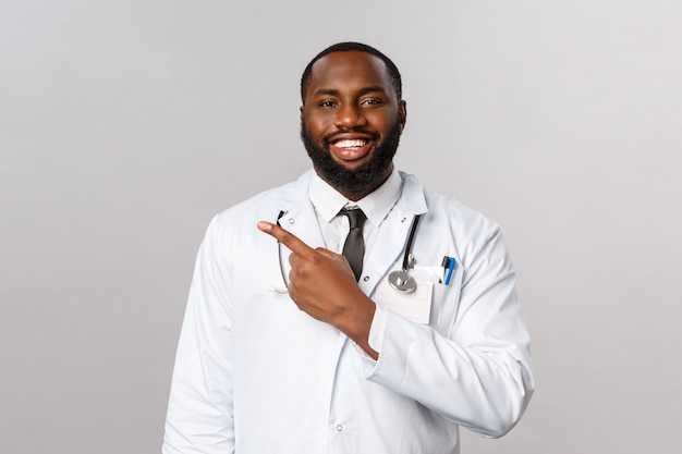 Ziekenhuiscontrole en gezondheidszorgconcept. knappe enthousiaste afro-amerikaanse bebaarde arts legt uit hoe het voorschrift in het ziekenhuis moet worden gevolgd, nodig de patiënt uit naar de kliniek en wijs naar links