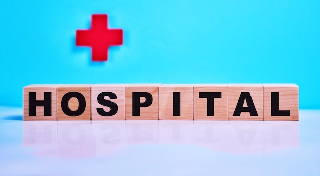 Ziekenhuisinscriptie op houten kubussen op een blauwe, op de van een rood kruis.
