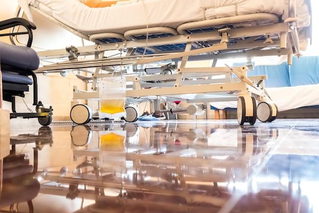 Ziekenhuiskamer met plastic zak die op een ziekenhuisbed hangt om urine op te vangen na een operatie.