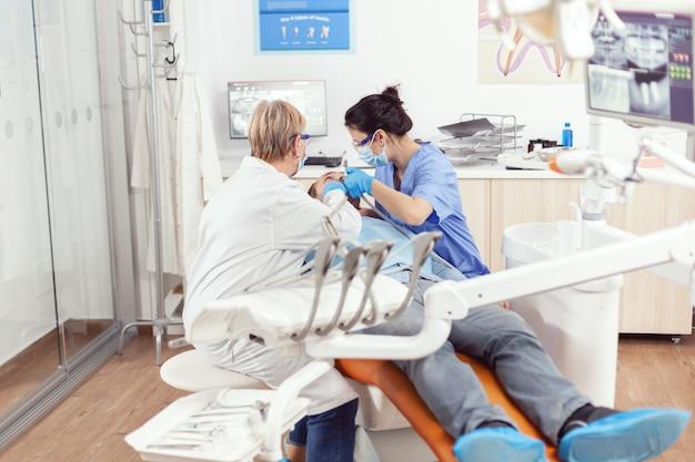 Ziekenhuistandartsenteam dat tanden van zieke man schoonmaakt die zich voorbereidt op stomatologische chirurgie tijdens stomatologische inspectie