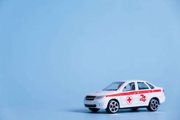 Ziekenwagenauto op blauwe muur. een medische nooddienst. toy medical voertuigmodel.