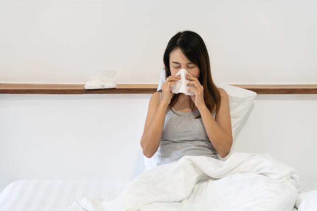 Ziekte meisje zittend op bed haar neus snuiten op een weefsel gezondheidszorg, allergisch voor hooikoorts. detailopname