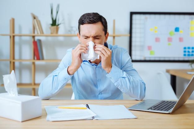 Ziekte op het werk. boos brunette ogen sluiten terwijl neus afvegen en ellebogen op tafel zetten